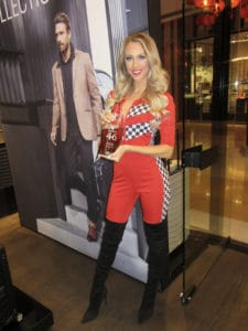 blonde model in red racing suits promotes makers mark bourbon ar porsche design in las vegas